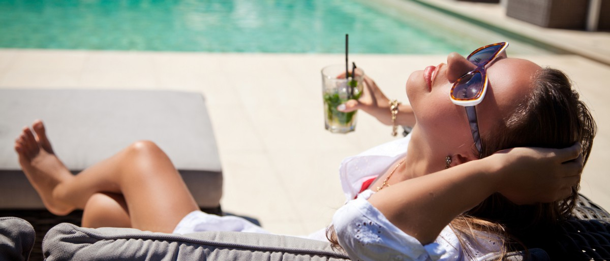 Woman drinking cocktail at poolside